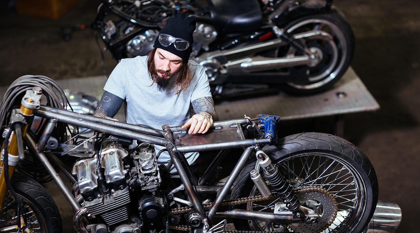 Portrait of tattooed man working in garage customizing motorcycle