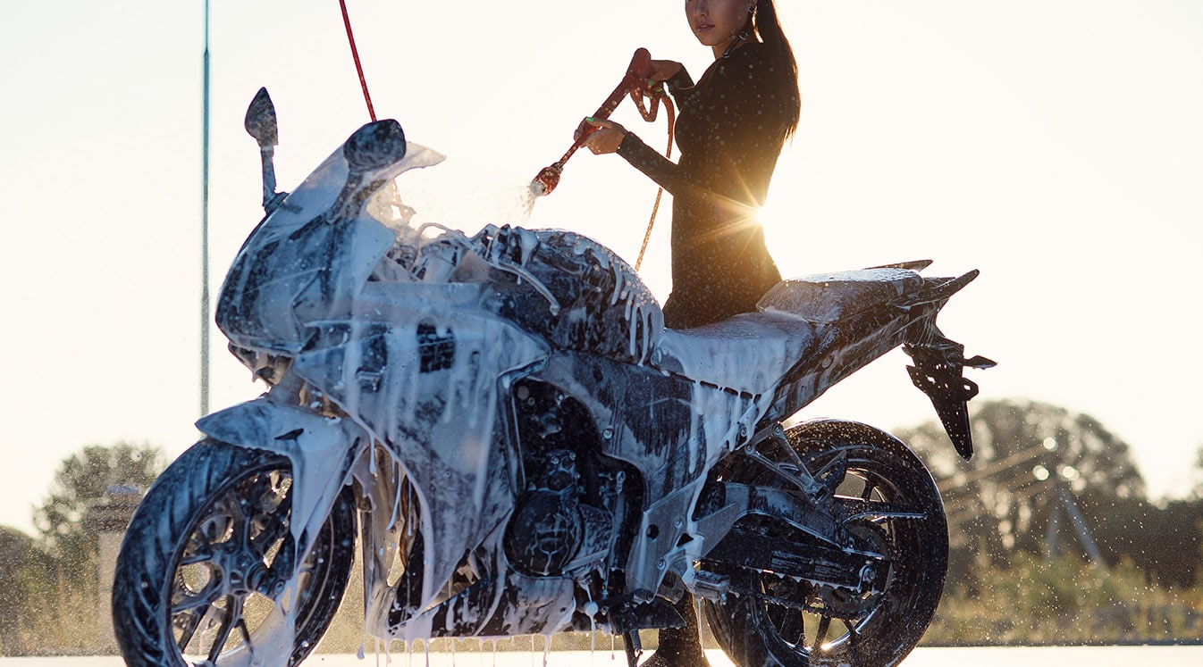 woman washes a motorcycle at self service car wash