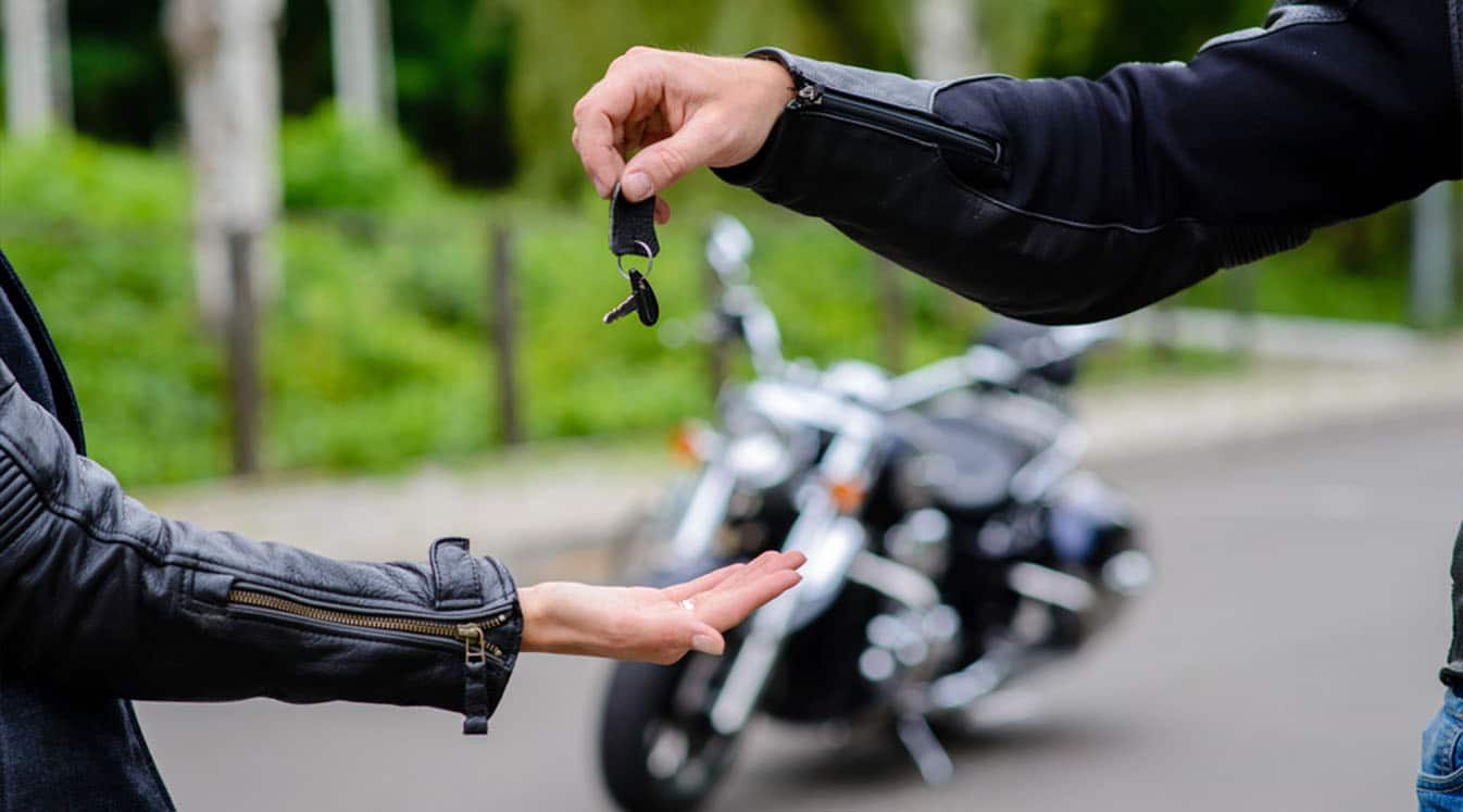 Hands pass the keys to the motorbike